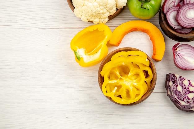 Draufsicht frisches gemüse grüne tomate geschnittener rotkohl geschnittener zwiebel geschnittener paprika-kürbis in schalen auf weißer holzoberfläche mit freiem platz