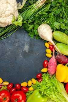 Draufsicht frisches gemüse kirschtomaten cumcuat blumenkohl rettich frühlingszwiebel petersilie zucchini mit freiem platz