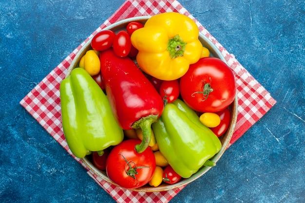 Draufsicht frisches gemüse kirschtomaten verschiedene farben paprika tomaten cumcuat auf platte auf rot weiß kariertem küchentuch auf blauer oberfläche