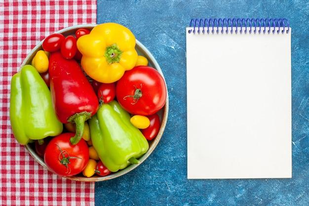 Draufsicht frisches gemüse kirschtomaten verschiedene farben paprika tomaten cumcuat auf platte auf rotem und weiß kariertem tischtuch notizbuch auf blauem tisch