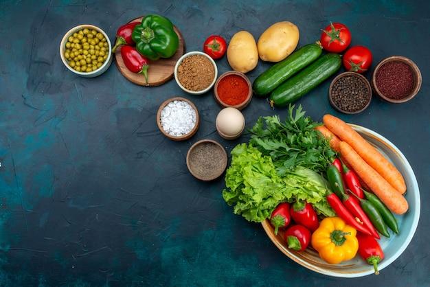 Draufsicht frisches gemüse mit gemüse und gewürzen auf dem dunkelblauen schreibtisch-snack-mittagssalat-gemüselebensmittel