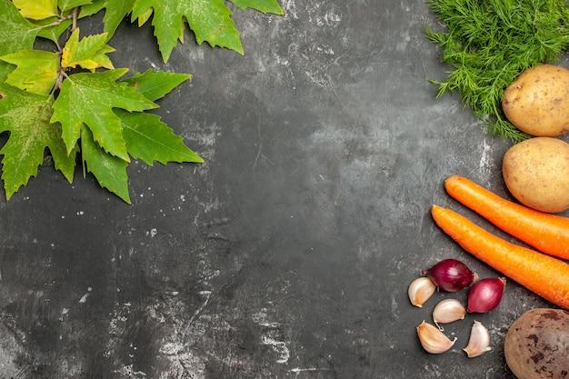 Draufsicht frisches gemüse mit grünen blättern auf grauer oberfläche