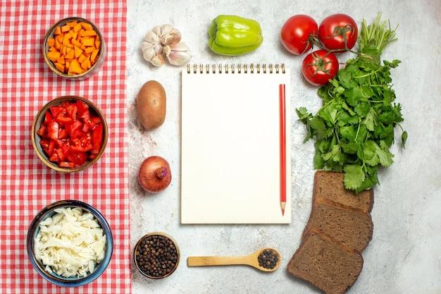 Draufsicht frisches gemüse tomaten pfeffer und kohl auf hellem weißraum
