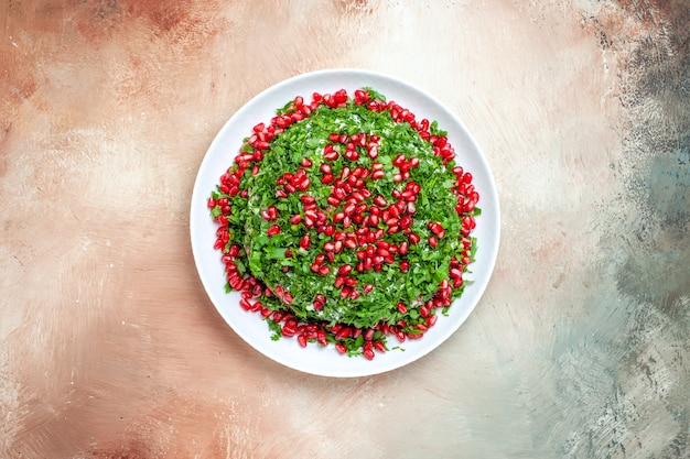 Draufsicht frisches grün mit geschälten granatäpfeln auf dem leuchttisch fruchtgrün