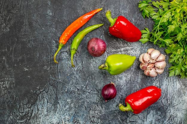 Draufsicht frisches grün mit paprika und knoblauch auf hellgrauem tisch