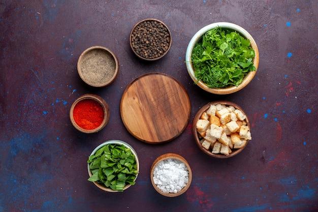 Draufsicht frisches grün mit zwieback und gewürzen auf dem dunklen tisch, mahlzeit suppe grünes essen