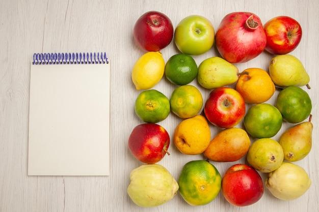 Draufsicht frisches obst äpfel mandarinen birnen und andere früchte auf weißem schreibtisch früchte reifer baum milde frische viele