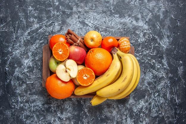 Draufsicht frisches obst bananen äpfel orangen zimtstangen auf holztablett auf dem tisch