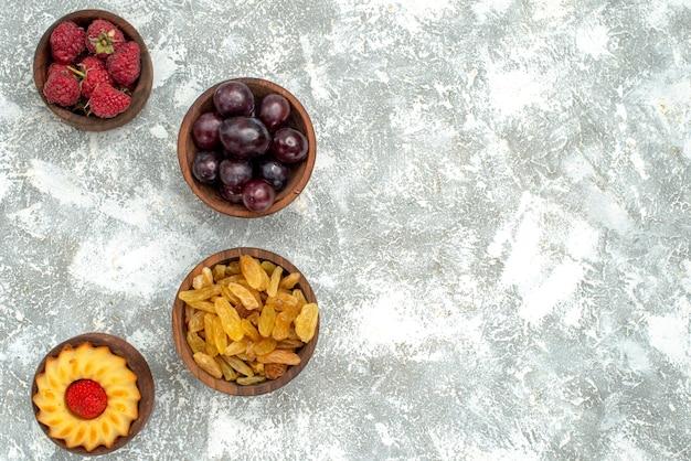 Draufsicht frisches obst mit rosinen auf weißer backgruond-frucht-beeren-kuchenfarbe Kostenlose Fotos