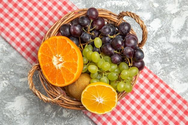 Draufsicht frisches obst, trauben und orangen im korb auf weißer oberfläche, reifes, ausgereiftes vitamin frisch