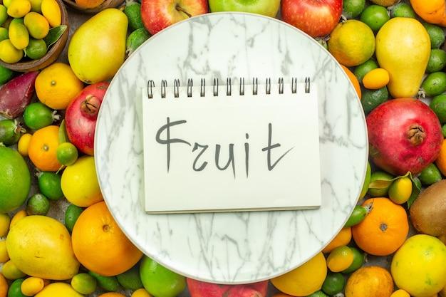 Draufsicht frisches obst verschiedene reife früchte auf weißem hintergrund beerendiät leckere farbe gesundheit reife baumfrucht