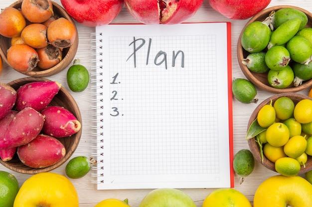 Draufsicht frisches obst zusammensetzung verschiedene früchte mit plan geschriebenen notizblock auf weißem hintergrund