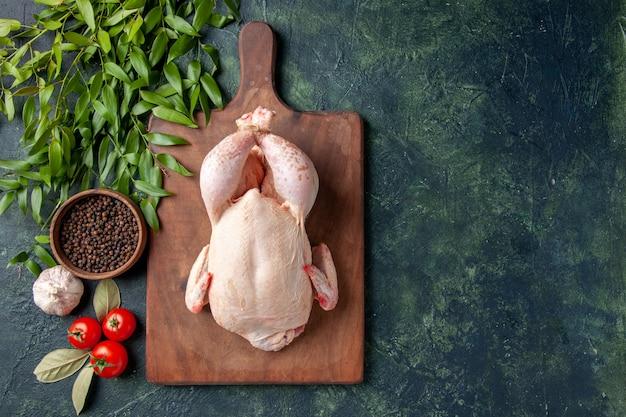 Draufsicht frisches rohes huhn mit tomaten auf dunkelblauem hintergrund küche restaurant mahlzeit tierfoto bauernhof essen hühnerfleisch farbe