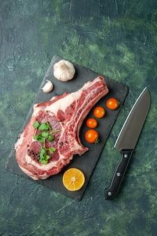 Draufsicht frischfleischscheibe mit orangefarbenen tomaten auf dunkelblauem hintergrund essen fleisch küche tier huhn farbe kuh metzger
