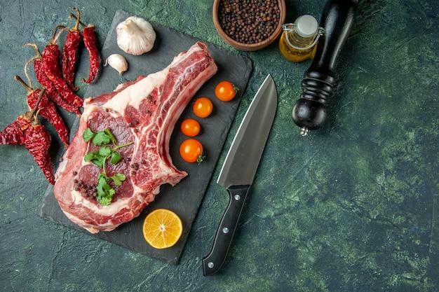 Draufsicht frischfleischscheibe mit orangefarbenen tomaten auf dunkelblauem hintergrund farbe lebensmittel fleisch küche tier huhn kuh metzger