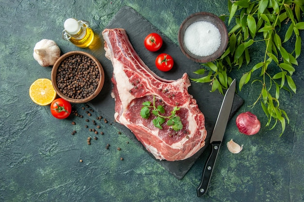 Draufsicht frischfleischscheibe mit tomaten und pfeffer auf dunkelblauem hintergrund küche tier kuh huhn lebensmittelfarbe metzger