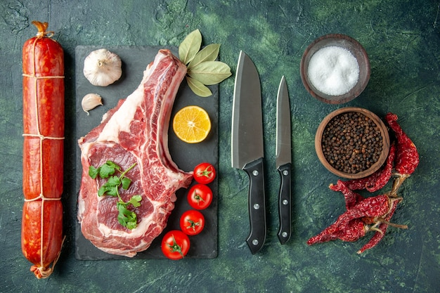 Draufsicht frischfleischscheibe mit wurst auf dunkelblauem hintergrund lebensmittel fleisch küche tier kuh metzger hühnerfarbe