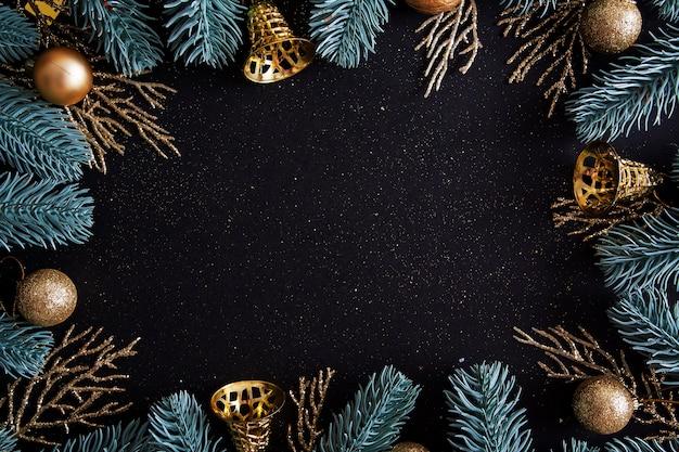 Draufsicht frohe weihnachten schwarzer hintergrund verziert mit frohes neues jahr-weihnachtsbaumzweigen und kugeln mit kopienraum. winterferienkartendekoration festliches spaßkonzept, flach gelegt.