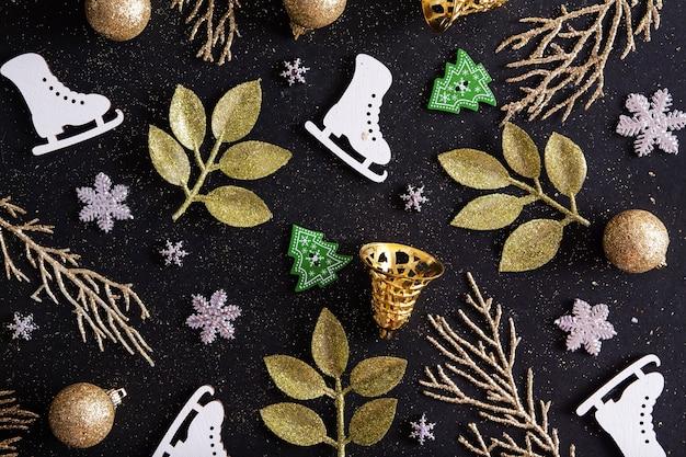 Draufsicht frohe weihnachten schwarzer hintergrund verziert mit weihnachtsbäumen, schneeflocken, schlittschuhen, glocken. winterferienmuster
