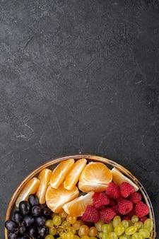 Draufsicht fruchtzusammensetzung erdbeeren trauben himbeeren und mandarinen innerhalb tablett auf dem dunklen raum
