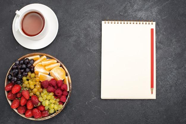 Draufsicht fruchtzusammensetzung erdbeeren trauben himbeeren und mandarinen mit tasse tee auf dunklem schreibtisch