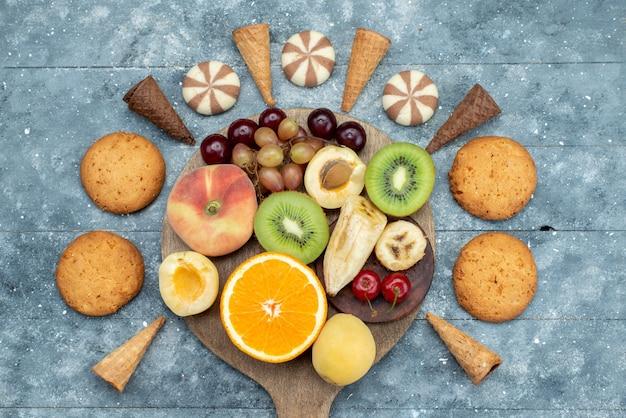 Draufsicht fruchtzusammensetzung geschnitten und ganz mit keksen auf dem hellen schreibtischfrucht exotischen kekszucker