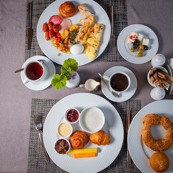 Draufsicht frühstückseier, oliven, omelett, croissant in tellern und tasse tee auf dem tisch