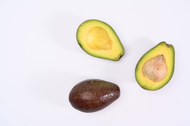 Draufsicht ganz und halb avocado mit samen auf weißem hintergrund.