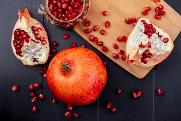 Draufsicht ganze hälften und geschälter granatapfel auf einem schneidebrett auf einem schwarzen tisch