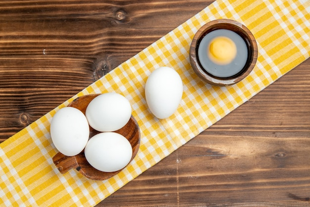 Draufsicht ganze rohe eier auf dem braunen hölzernen tischnahrungsmittelfrühstücks-holzeier