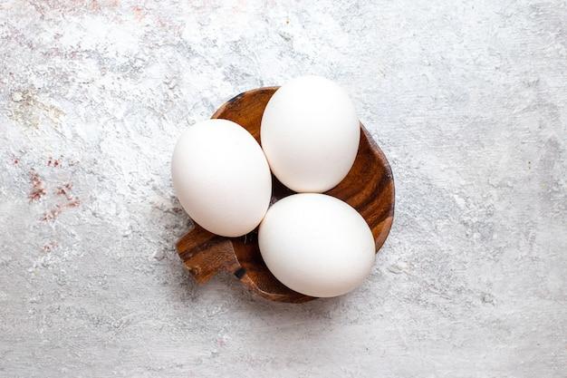 Draufsicht ganze rohe eier auf roher frühstücksmahlzeitnahrung der weißen oberfläche ei