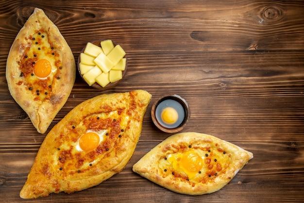 Draufsicht gebackene eierbrote frisch aus dem ofen auf braunem hölzernen schreibtischteigbrotbrötchenfrühstück