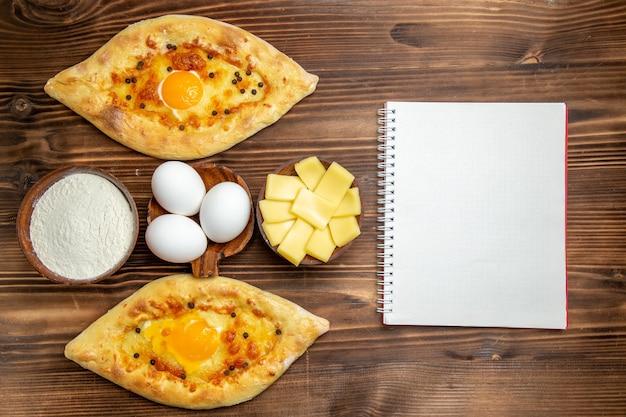 Draufsicht gebackene eierbrote frisch aus dem ofen auf dem braunen hölzernen schreibtisch teig eierbrötchen frühstücksbrot