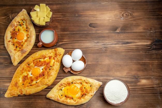 Draufsicht gebackene eierbrote frisch aus dem ofen auf holzoberflächenteig-eierbrötchen-frühstücksbrot