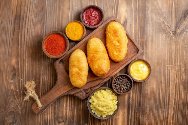 Draufsicht gebackene kartoffel-hotcakes mit gewürzen auf braunem holz-schreibtisch-kuchen-backen-teig-mahlzeit-ofenkartoffel