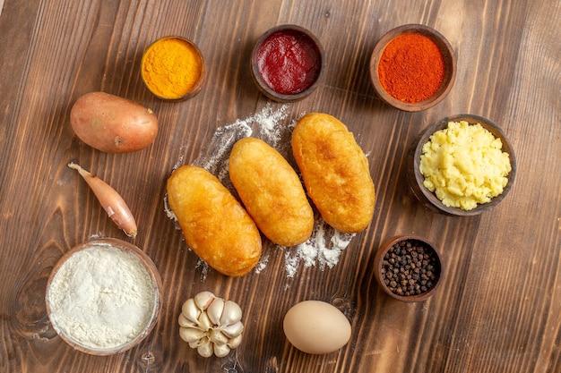 Draufsicht gebackene kartoffel-hotcakes mit gewürzen auf braunem holz-schreibtisch-kuchen-backen-teig-ofen-kartoffel-mahlzeit
