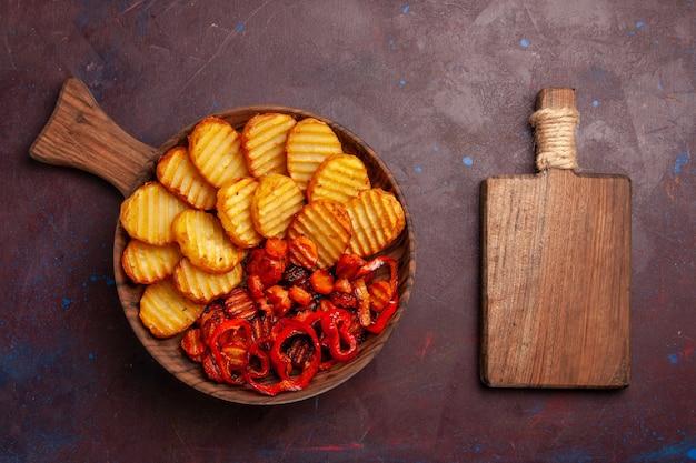 Draufsicht gebackene kartoffeln mit gekochtem gemüse innerhalb platte auf dem dunklen raum