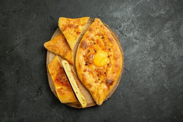 Draufsicht gebackenes eierbrot köstlich frisch vom ofen auf dem dunkelgrauen raum