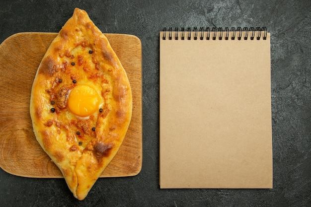 Draufsicht gebackenes eierbrot köstliches teigbrötchen frisch aus dem ofen auf dunklem raum