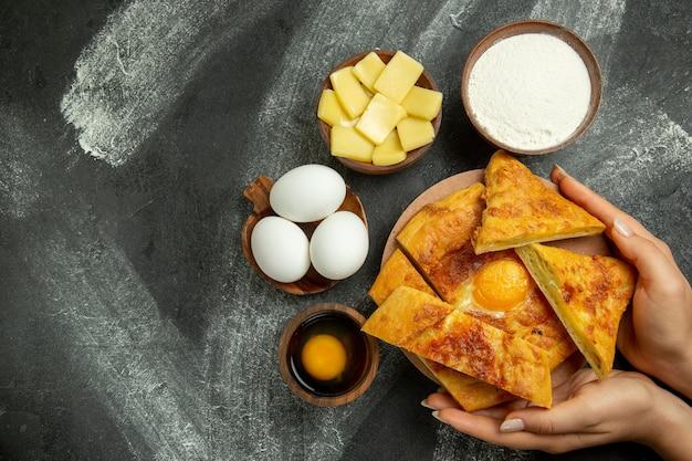 Draufsicht gebackenes eierbrot mit frischen eiern und geschnittenem käse auf grauem schreibtisch