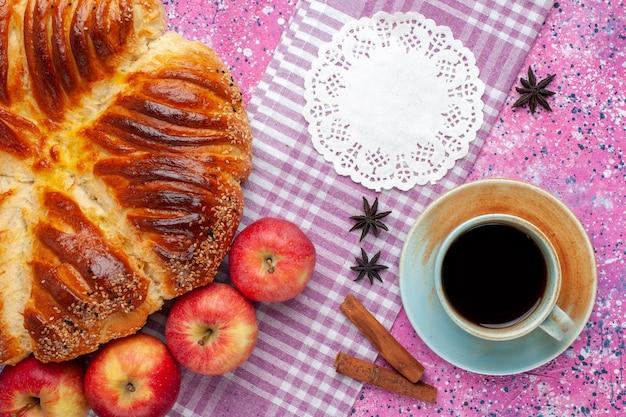 Draufsicht gebackenes gebäck mit zimtäpfeln und tasse tee auf rosa schreibtisch.