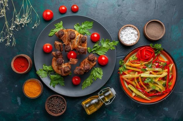 Draufsicht gebratene fleischscheiben mit gemüse und gewürzen auf der dunkelblauen oberfläche gemüsemehl lebensmittel fleisch abendessen gesundheit
