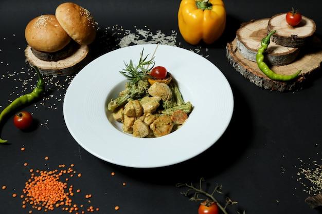 Draufsicht gebratene hühnerbrust mit brokkoli in einem teller mit paprika-chili-pfeffer und brot