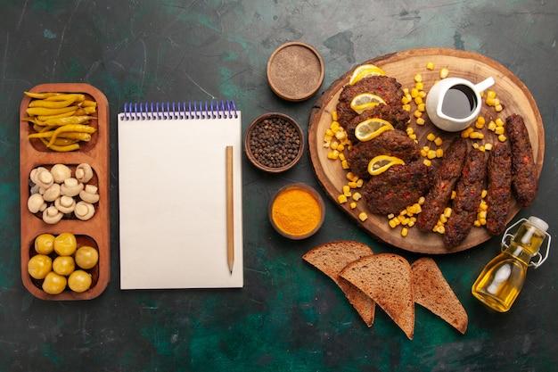 Draufsicht gebratene leckere schnitzel mit maisbrotlaib und gewürzen auf grüner oberfläche fleischmehl lebensmittelgemüsekochen