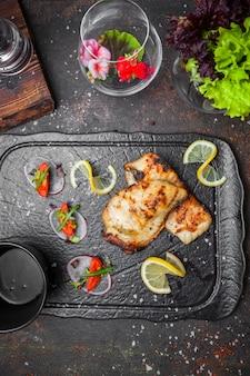 Draufsicht gebratener fisch mit tomate und zwiebel