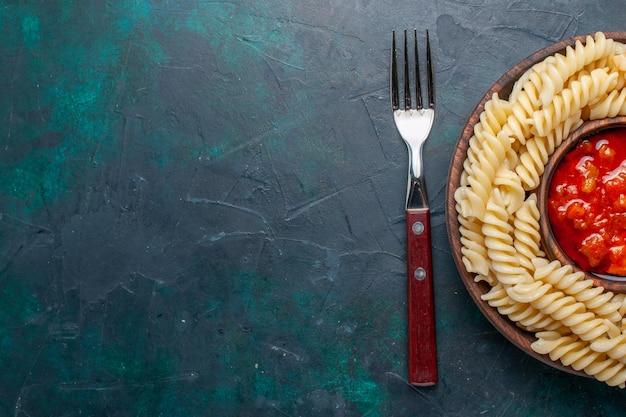Draufsicht geformte italienische nudeln mit tomatensauce und gabel auf dunkelblauem hintergrund