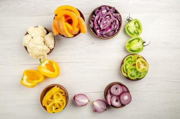 Draufsicht gehacktes gemüse geschnitten rotkohl geschnitten kürbis geschnitten gelbe paprika geschnitten zwiebel geschnitten grüne tomaten blumenkohl in schalen auf weißem tisch