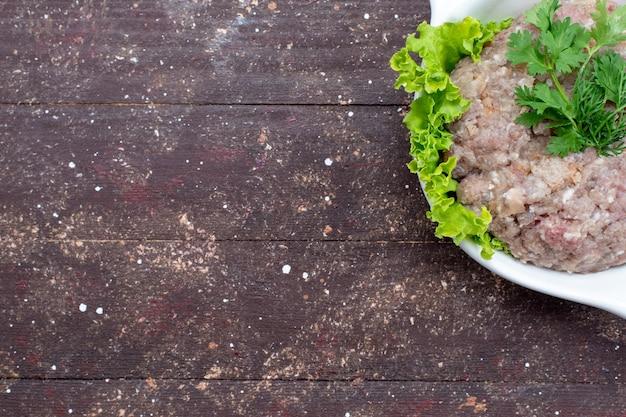 Draufsicht gehacktes rohes fleisch mit grün innerhalb platte auf dem braunen hintergrundfleisch rohkostmehl grün