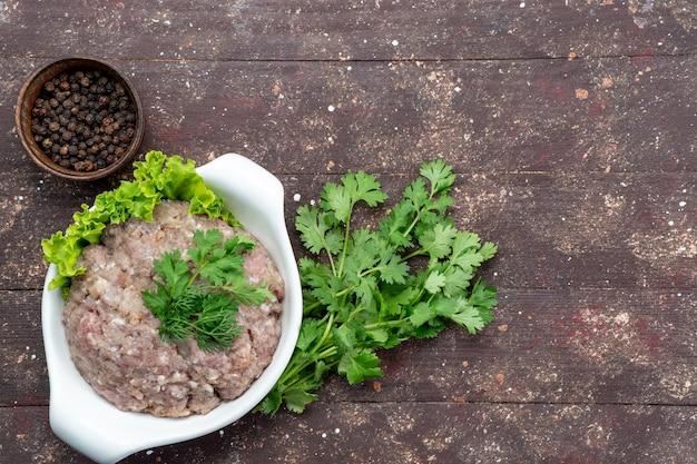 Draufsicht gehacktes rohes fleisch mit grün innerhalb platte mit gewürzen auf dem braunen hintergrund fleisch rohkost mahlzeit grünes foto