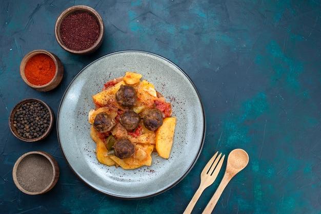 Draufsicht gekochte geschnittene kartoffeln mit fleischbällchen innerhalb teller mit gewürzen auf dunkelblauem schreibtisch.